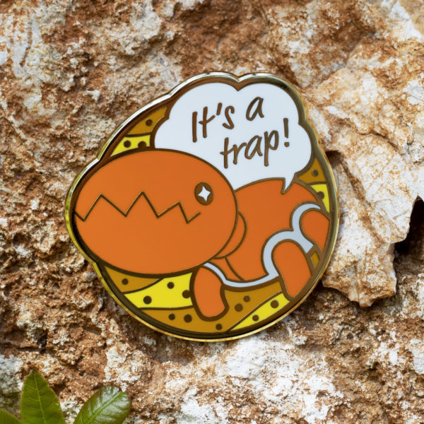 Trapinch hard enamel pin on a beautiful rock.